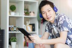 Um homem que guarda a tabuleta com os fones de ouvido para escuta a música fotografia de stock royalty free