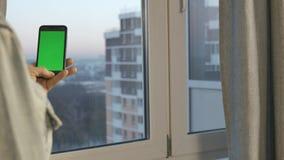 Um homem que guarda um telefone com uma tela verde Está pela janela Fim acima video estoque