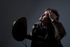 Um homem que guarda um chapéu de vaqueiro e que olha acima pensativamente. Imagens de Stock