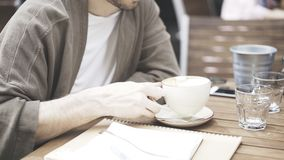 Um homem que guarda uma xícara de café em um café fora Imagens de Stock Royalty Free