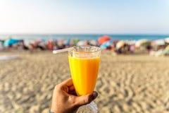 Um homem que guarda um vidro fresco do suco de laranja com uma palha na frente da praia Imagens de Stock