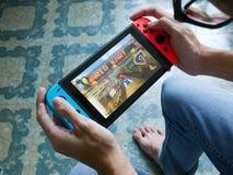 Um homem que joga Mario Kart 8 de luxe no interruptor de Nintendo imagens de stock royalty free