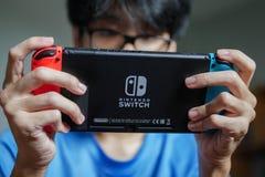 Um homem que joga o interruptor de Nintendo fotografia de stock