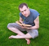 Um homem que lê um livro na grama Fotos de Stock