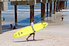 Um homem que leva uma prancha amarela anda ao longo da praia perto da ressaca Fotos de Stock Royalty Free