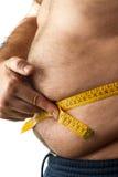 Um homem que mede o seu gordura da barriga Imagens de Stock