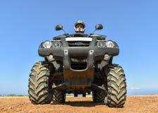 Um homem que monta ATV na areia em um capacete Fotografia de Stock
