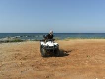 Um homem que monta ATV na areia em um capacete Imagem de Stock Royalty Free