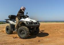 Um homem que monta ATV na areia em um capacete Imagens de Stock