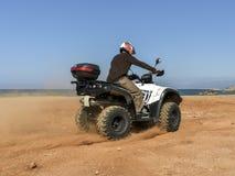 Um homem que monta ATV na areia em um capacete Fotos de Stock Royalty Free