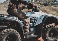 Um homem que monta ATV na areia em um capacete Foto de Stock Royalty Free