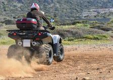 Um homem que monta ATV na areia em um capacete Fotografia de Stock Royalty Free