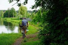 Um homem que monta uma bicicleta com artes de pesca fotografia de stock royalty free