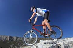Um homem que monta uma bicicleta de montanha Fotos de Stock Royalty Free
