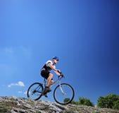 Um homem que monta uma bicicleta de montanha em uma inclinação Imagens de Stock