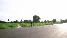 Um homem que monta uma bicicleta em um céu claro em Tailândia video estoque