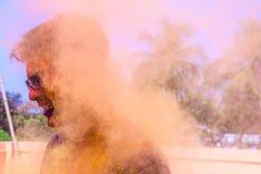 Um homem que obtém regado com as cores do holi durante o festival do holi em india imagem de stock