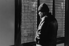 Um homem que olha fixamente fora no estação de caminhos-de-ferro em Jackson Heights Fotografia de Stock