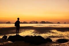 Um homem que olha o nascer do sol bonito no mar foto de stock