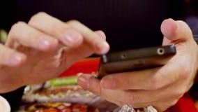 Um homem que olha um smartphone que est? realizando em suas m?os video estoque