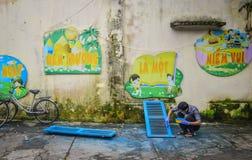 Um homem que pinta portas de madeira na rua imagem de stock royalty free