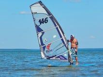Um homem que prepara-se para o windsurfe no lago Plescheevo perto da cidade de Pereyaslavl-Zalessky em Rússia imagem de stock