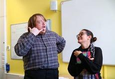 Um homem que puxa uma cara parva para fazer uma mulher rir Foto de Stock Royalty Free