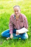 Um homem que relaxa no parque, lendo um livro e um sorriso, olhando Foto de Stock