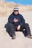Um homem que senta-se com o telefone celular na praia Imagem de Stock Royalty Free