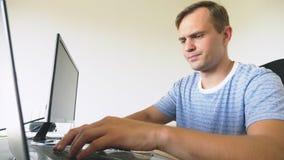 Um homem que senta-se em uma mesa em casa, trabalhando em casa o computador e o portátil vídeos de arquivo