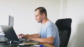 Um homem que senta-se em uma mesa em casa, trabalhando em casa o computador e o portátil video estoque