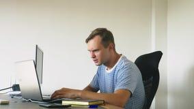 Um homem que senta-se em uma mesa em casa, trabalhando em casa o computador e o portátil filme