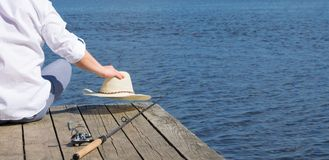 Um homem que senta-se no cais e que guarda um chapéu, encontrando-se ao lado de uma vara de pesca, no fundo do lago fotos de stock