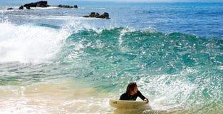 Um homem que skimboarding na praia grande em Maui Fotos de Stock