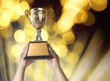 um homem que sustenta um copo do troféu do ouro com boke da luz do ouro do bastract Imagens de Stock Royalty Free