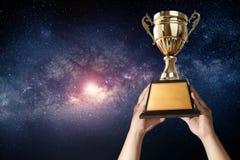 um homem que sustenta um copo do troféu do ouro com fundo do céu da Via Látea Imagens de Stock Royalty Free