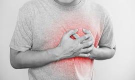 Um homem que toca em seu coração, com destaque vermelho do cardíaco de ataque, da parada cardíaca, de outro doença cardíaca e de  fotografia de stock