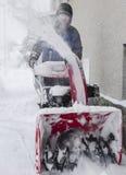 Um homem que trabalha com uma máquina de sopro da neve imagens de stock royalty free