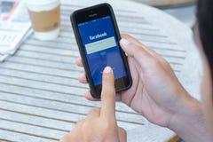 Um homem que usa a aplicação de Fackbook no iphone fotos de stock royalty free