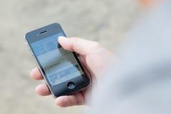 Um homem que usa a aplicação de Feacbook no iPhone 4 com a tela de exposição seriamente quebrada Imagem de Stock