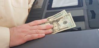 Um homem que veste a camisa colorida leve oficial guarda seu nand direito em vinte dólares imagem de stock royalty free