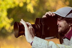 Um homem que veste um tampão com uma câmera de filme velha Fotos de Stock