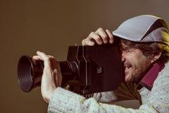 Um homem que veste um tampão com uma câmera de filme velha Foto de Stock