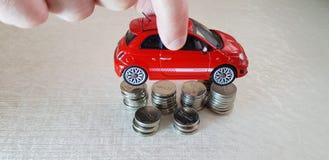 Um homem realiza em seu brinquedo vermelho do abarth da autorização 500 dos dedos sobre uma pilha das moedas israelitas de um she imagens de stock royalty free