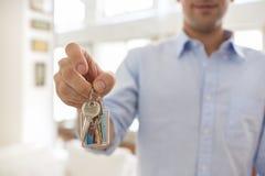 Um homem realiza em sua mão as chaves de sua casa, internas. Fotografia de Stock Royalty Free