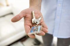 Um homem realiza em sua mão as chaves de sua casa, internas. Foto de Stock Royalty Free