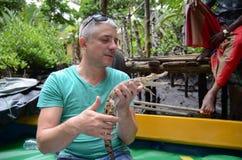Um homem realiza nas mãos um crocodilo pequeno fotografia de stock