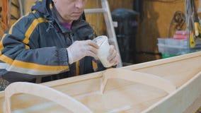 Um homem recolhe um barco feito da madeira É contratado no trabalho manual filme