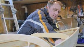 Um homem recolhe um barco feito da madeira É contratado no trabalho manual vídeos de arquivo
