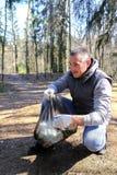 Um homem recolhe o lixo Põe-no em um saco de lixo O problema da polui??o ambiental Polui??o ecol?gica Problema da ecologia foto de stock royalty free